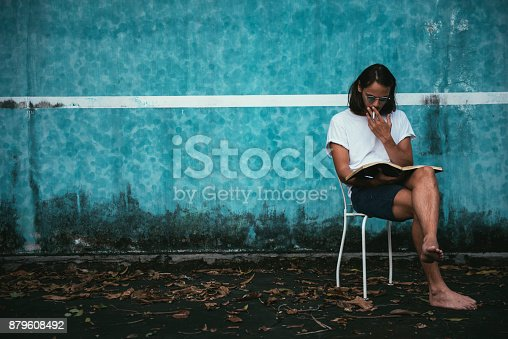 istock Hipster man reading a book  879608492