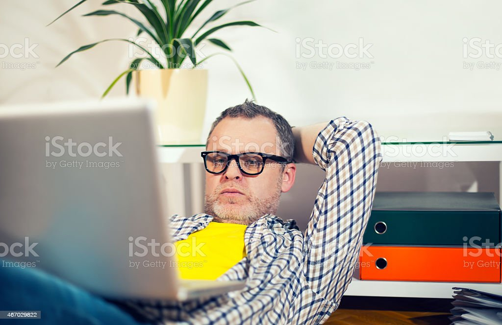 Hipster Man Sitting On Office Floor With Laptop stock photo
