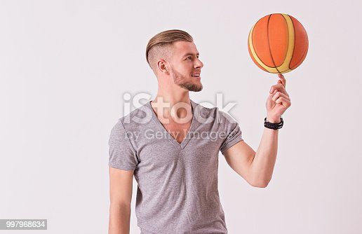 Bearded hipster in t-shirt spinning basketball ball on index finger and smiling while isolated on white background. Young sports man exercising with ball. Healthy lifestyle and sport bets concept