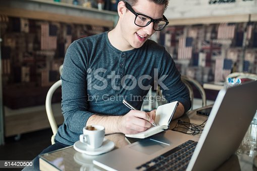istock Hipster man taking notes from his laptop to his notebook, 514420500