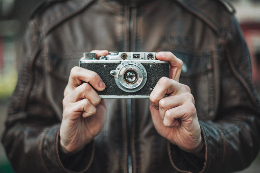 Hipster man taking photo with retro camera