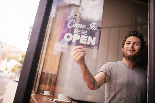 hipster man turning opening sign on door coffee shop - open sign stock pictures, royalty-free photos & images
