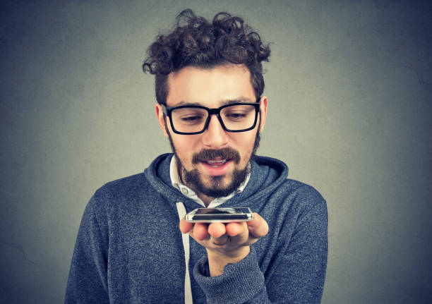 hipster man using a smart phone voice recognition function - dictaphone stock pictures, royalty-free photos & images