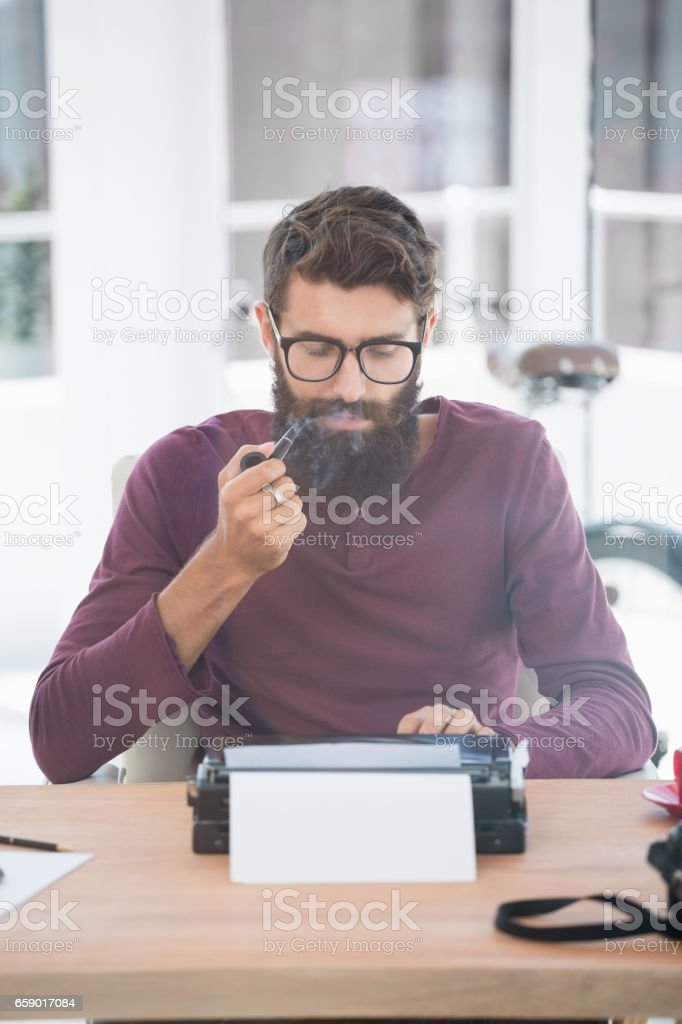 Hipster man using a typewriter and smoking the pipe royalty-free stock photo