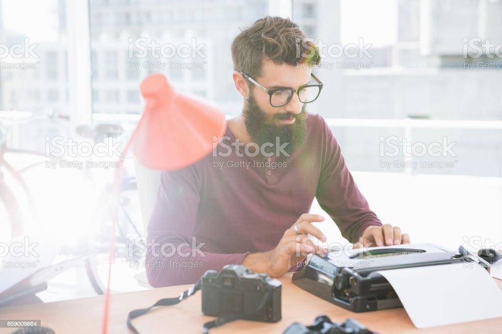 Hipster man using a typewriter royalty-free stock photo