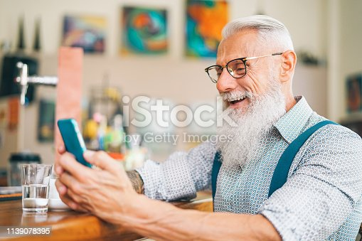 istock Hipster man using mobile phone while sitting in a bar - Senior male watching on new trends smartphone apps for social media - Technology and people lifestyle concept 1139078395