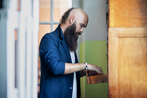 668340340 istock photo Hipster man using old paper card catalog to find some information 1026060924