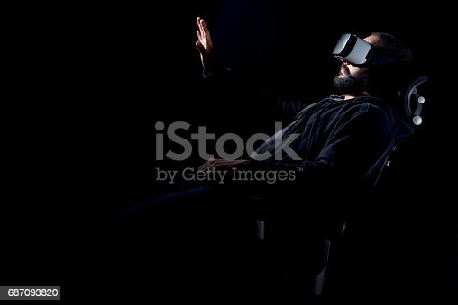 687096686istockphoto Hipster man wearing virtual reality goggles. Black background VR concept. 687093820
