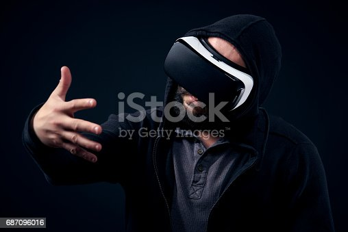 687096686istockphoto Hipster man wearing virtual reality goggles. Black background VR concept. 687096016