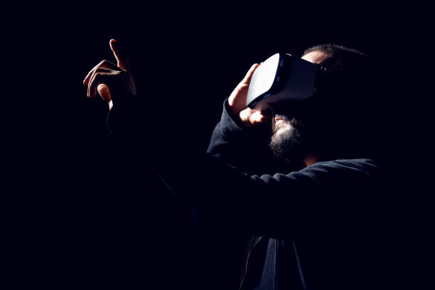 Hipster man wearing virtual reality goggles. Black background VR concept. stock photo