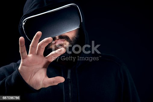 687096686istockphoto Hipster man wearing virtual reality goggles. Black background VR concept. 687096786