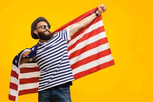 Hipster man with flag on orange Young hipster in hat and sunglasses posing cheerfully with American flag looking away on orange background. american flag tattoos for men stock pictures, royalty-free photos & images
