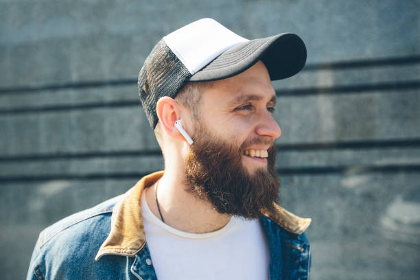 Hipster man with sport in-ear wireless headphones listening to music and using a tablet pc stock photo