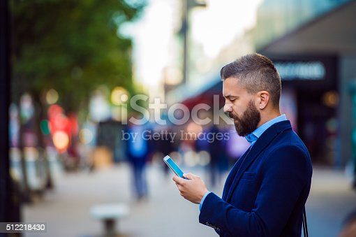Hipster manager holding smartphone, texting, reading, writing, searching something, outside in the street