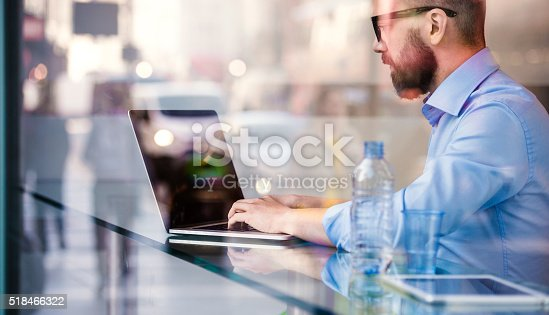 istock Hipster manager in cafe, working on laptop by window 518466322