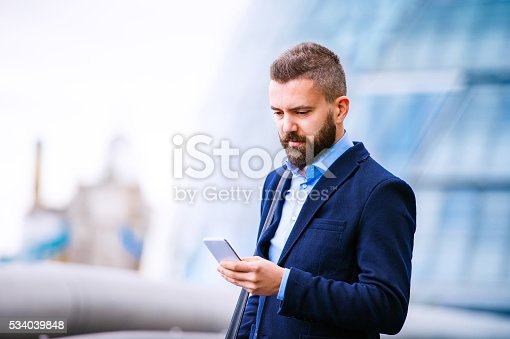 Hipster manager holding a smart phone, writing a message, City Hall, London