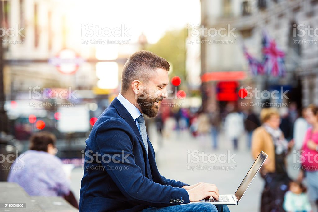 Hipster manager working on laptop on sunny Piccadilly Circus, Lo stock photo