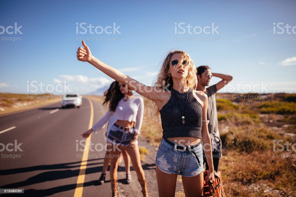 Hipster Multi-Ethnic Group of friends Hitchhiking on Highway stock photo
