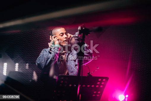 Young hipster African-American singer with headphones performing song and recording music in recording studio