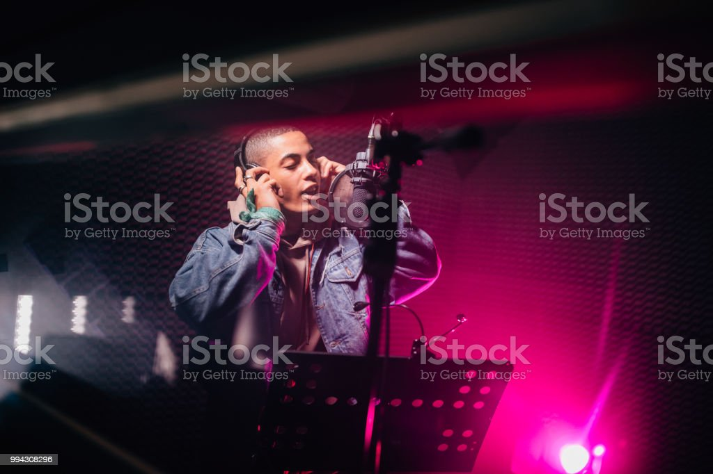 Hipster musician singing and recording songs in professional music studio stock photo