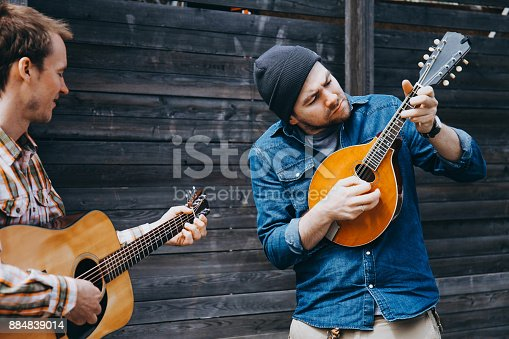 istock Hipster musicians are playing on the street. 884839014