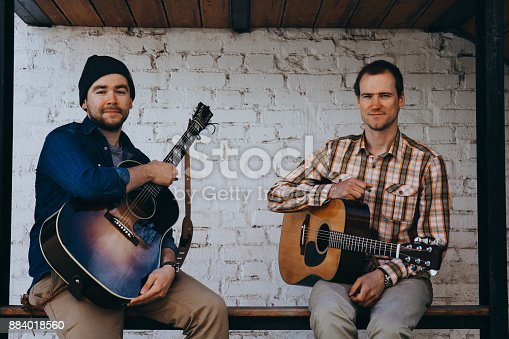 istock Hipster musicians sitting on the street. 884018560