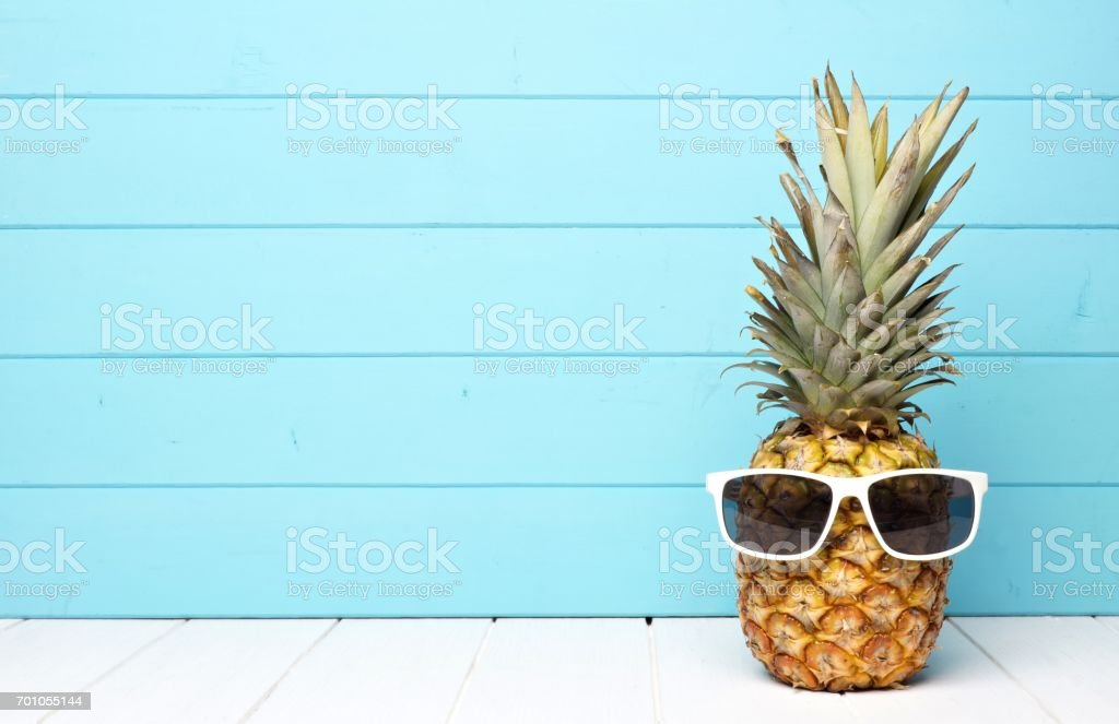 Hipster pineapple with sunglasses against blue wood stock photo