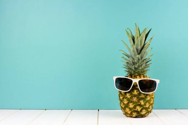 Hipster pineapple with sunglasses against turquoise stock photo