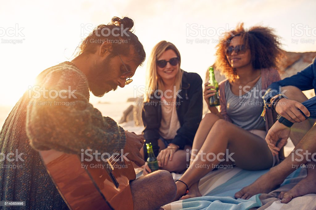 Hipster playing guitar for friends at the beach stock photo