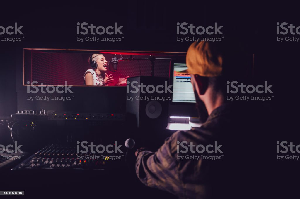 Hipster pop music artist recording song at professional music studio stock photo
