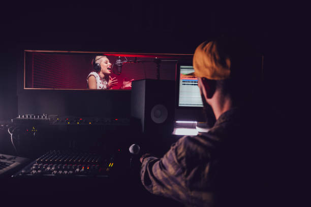 Hipster pop music artist recording song at professional music studio Hipster rock music singer and music producer recording song in professional music recording studio recording studio stock pictures, royalty-free photos & images
