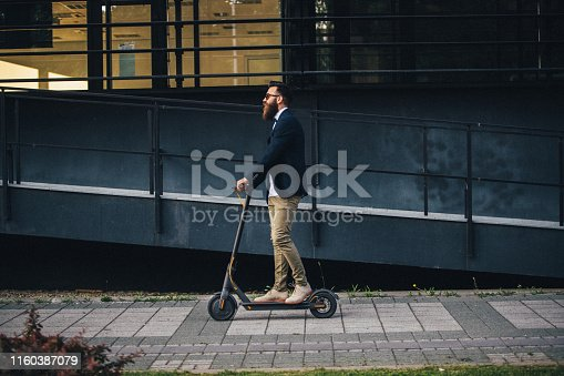 Hipster riding a scooter in the city