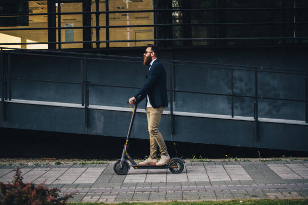 hipster riding a scooter in the city - electric push scooter stock photos and pictures