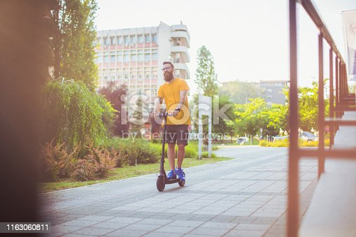 A young bearded man in a yellow t-shirt enjoying a ride on an electric scooter in a residential area of the city.