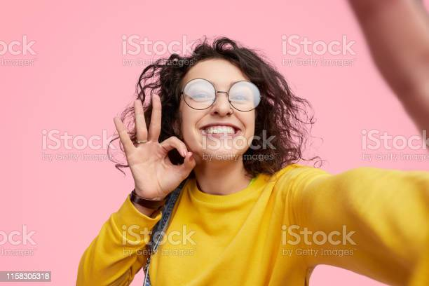 Hipster showing approving gesture and taking selfie picture id1158305318?b=1&k=6&m=1158305318&s=612x612&h=8v us6d0opefeyvoedmclwtwwluit9ecqw8yowjgkeo=