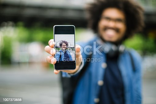 Close up of man showing his self portrait his his phone to camera. Hipster showing his smiling selfie.
