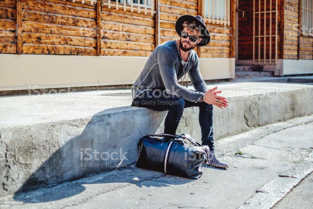 Hipster sentado y esperando seriamente - foto de stock