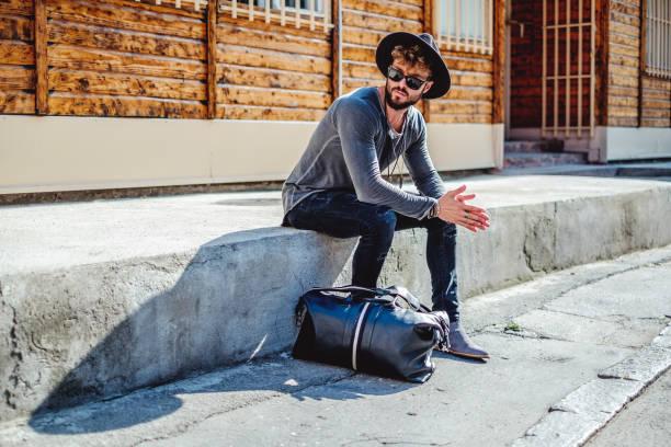hipster sitzen und warten ernst - männer mode stock-fotos und bilder