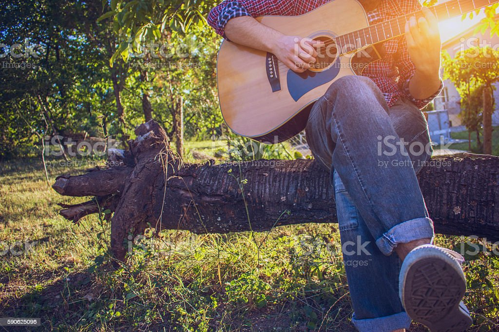 Hipster sitting on tree and playing acoustic guitar stock photo