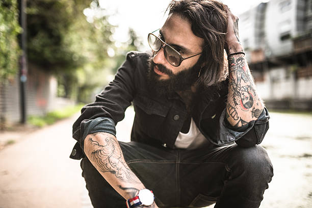 Hipster sitting pensive with tattoo stock photo