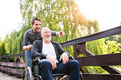 Young hipster son walking with disabled father in wheelchair on wooden bridge at park, pointing finger at something. Carer assisting disabled senior man.