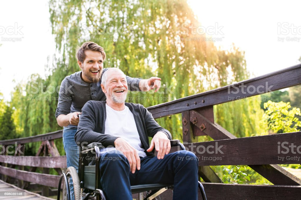 Hipster son walking with disabled father in wheelchair at park. stock photo