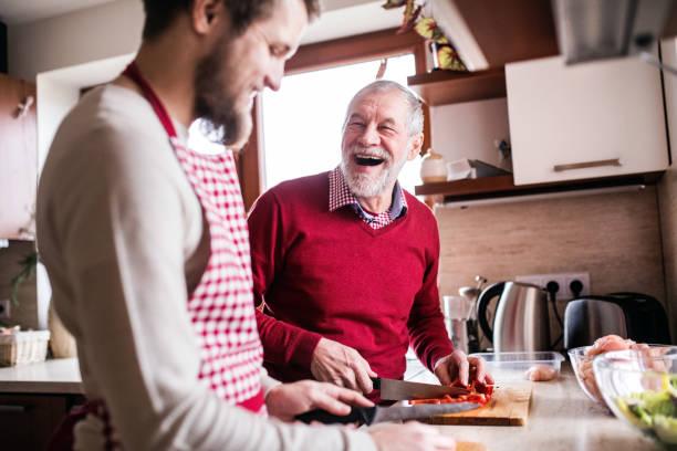 de zoon van de hipster met zijn hoge vader koken in de keuken. - koken toestand stockfoto's en -beelden