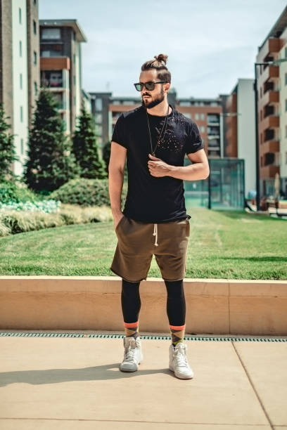 Hipster standing  seriously in the street Hipster in sportswear standing  seriously in the street man bun stock pictures, royalty-free photos & images