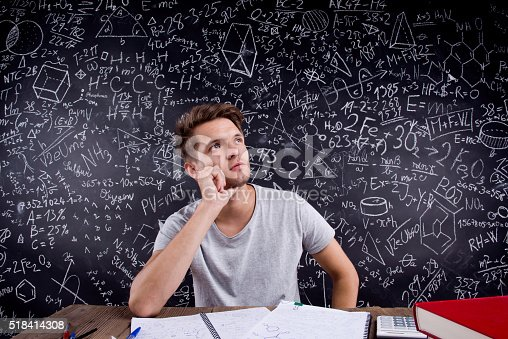 istock Hipster student doing his homework against a big blackboard 518414308