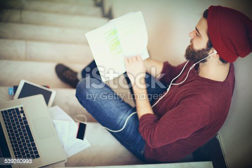 Hipster looking male student surfing the net on his tablet in hallway.Full grown beard and brown hair with red cap on.His books and laptop sitting beside him on the stairs.