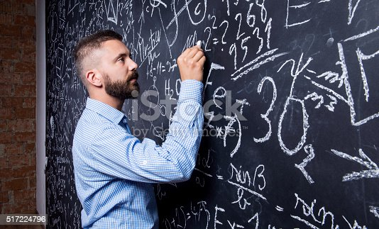 istock Hipster teacher writing on big blackboard with mathematical symb 517224796