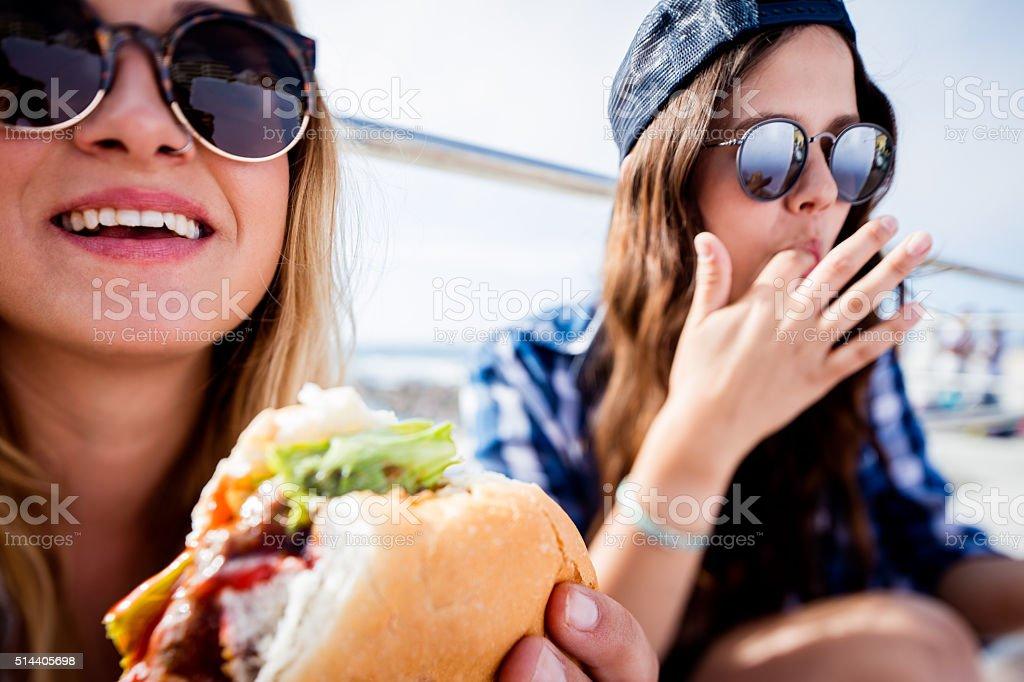 Hipster teen girl friends wearing sunglasses eating hamburgers t stock photo