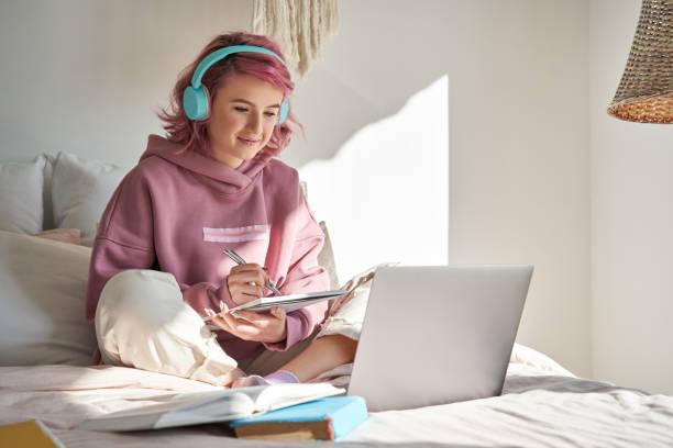 ピンクの髪の女の子の学生ヒップスターは、ベッドでオンラインウェビナー学習を見ます。 - gen z ストックフォトと画像