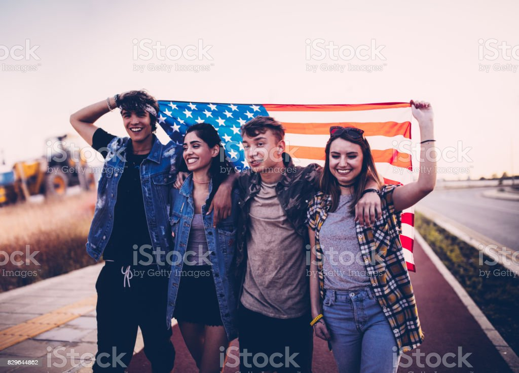 Hipster teenage friends marching the streets holding an American flag stock photo